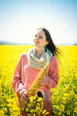 saxophonist: Young beautiful saxophonist with saxophone in yellow rapeseed field