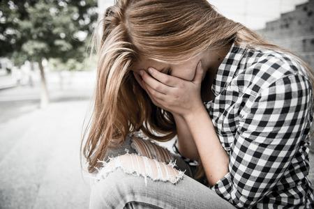 屋外に座って手で顔で落ち込んで不幸な十代の若者 写真素材