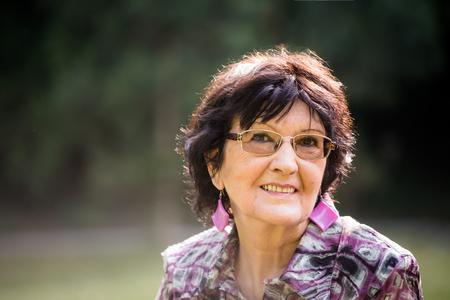 Portret van lachende senior vrouw buiten in de natuur