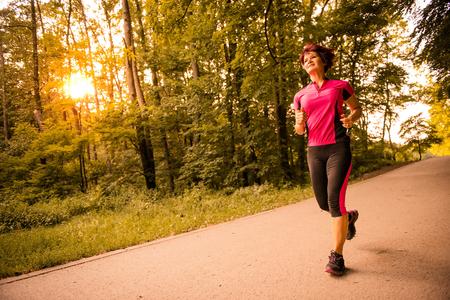 vital: Vital senior woman jogging in park at sunset