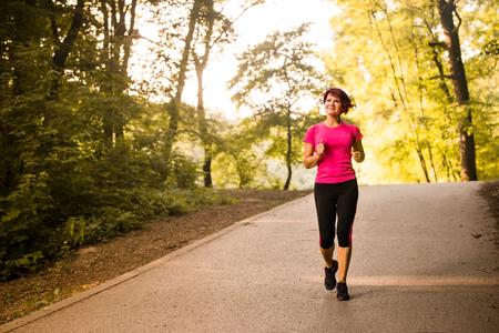 happy seniors: Vital senior woman jogging in park on summer evening