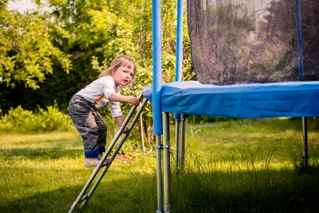 Little child climping on big trampoline - outdoors in backyard