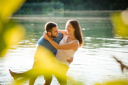 Young couple together on sunny summer day in lake, man carrying woman Foto de archivo