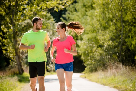 dos personas conversando: La gente corriendo juntos y hablando en la naturaleza soleado de verano