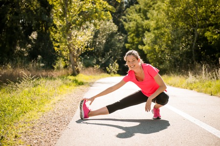 Young woman stretching her legs outdoor in nature before jogging