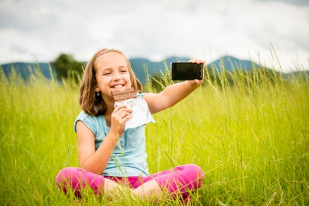 nature photo: Child is taking photo with mobile phone camera while eating chocolate outdoor in nature Stock Photo