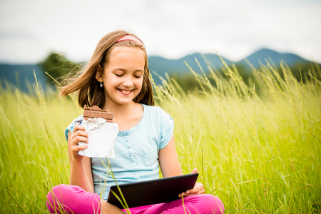 relishing: Child eating and relishing chocolate while watching tablet - outdoor in nature Stock Photo