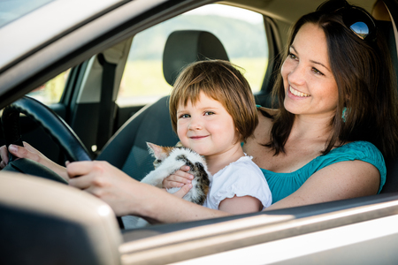 driving a car: Mother and child holding kitten pretend driving car sitting all on front driver seat Stock Photo