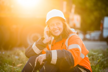 protective wear: Senior woman engineer wearing protective wear in work calling phone and relaxing - outdoor at sunset Stock Photo