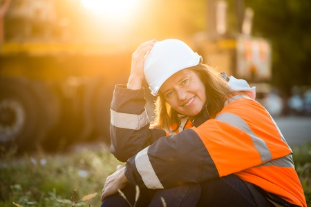 protective wear: Senior woman engineer wearing protective wear in work - outdoor at sunset Stock Photo