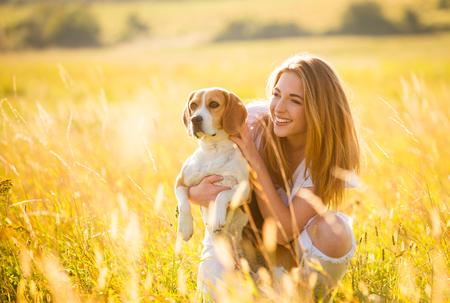 Tiener meisje met plezier met beagle hond buiten in de natuur op een zonnige zomerdag Stockfoto