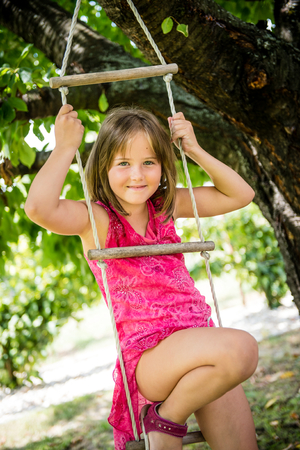 rope ladder: Happy child is playing on rope ladder outside in nature