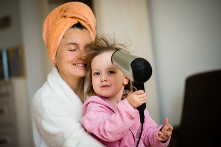 bathrobes: Mother and her little child in bathrobes having while drying hair