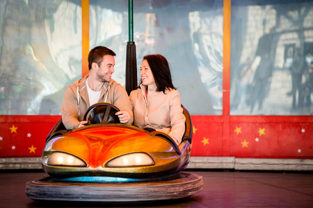 theme parks: Vienna, Prater - couple dating and riding on carousel car in entertainment park