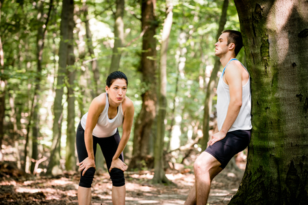 gasping: Young couple resting after jogging in nature, man leans against tree