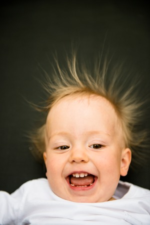 black hairs: Portrait of smiling baby with standing hair from static electricity