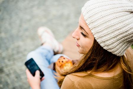 personas en la calle: Adolescente - mujer joven que come el mollete en la calle y mirando en el teléfono