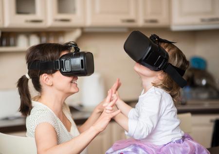 유행: 가정에서 가상 현실 헤드셋과 함께 노는 어머니와 아이