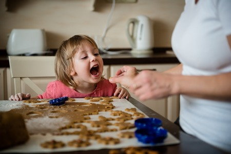 tastes: Mother giving her daughter to taste piece of dough