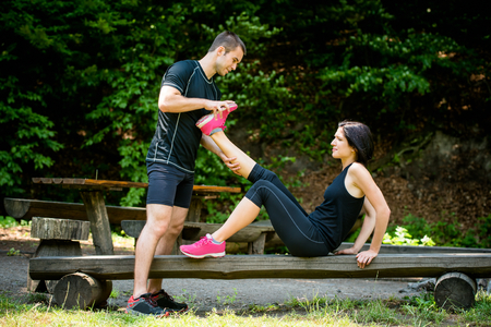 calf strain: Man stretches womans leg - muscle spasm after sport training