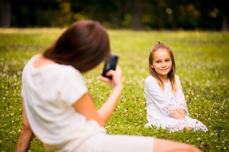 nature photo: Mother taking photo of her child with phone camera outdoor in nature
