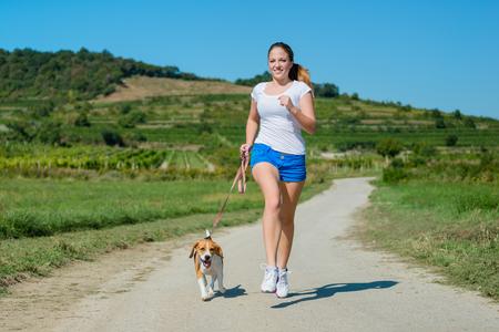 beagle: Beautiful teenage girl jogging with her pet (beagle dog) in nature