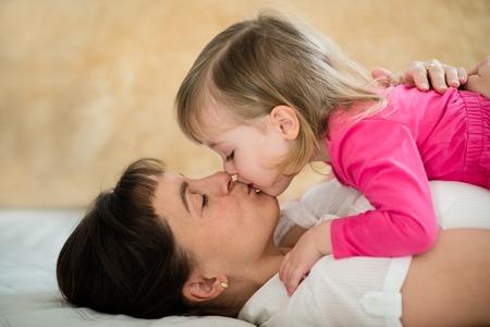 madre e hija: Madre con la hija besos - acostado en el sofá en casa