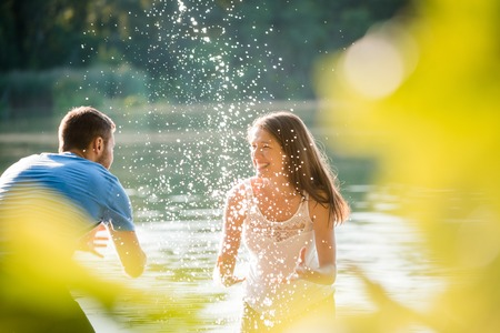 water splashing: Young couple splashing water on each other on sunny summer day in lake Stock Photo