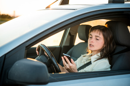 simultaneously: Young business woman driving car and looking simultaneously in her mobile phone Stock Photo