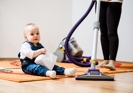 Cleaning up the room - woman with vacuum cleaner, baby sitting on floor Stock Photo