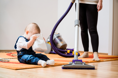 home keeping: Cleaning up the room - woman with vacuum cleaner, baby looking to biscuits packet Stock Photo