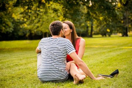 Junge lächelnde Paar sitzt und Küssen auf Gras - eine Frau barfuß mit Schuhen neben ihr