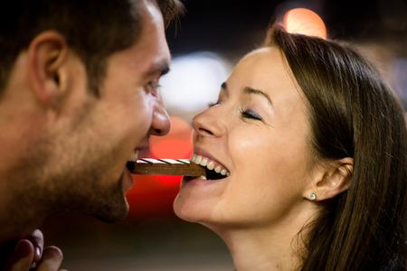 pareja comiendo: Pares jovenes que comen juntos un trozo de chocolate - en la calle por la noche