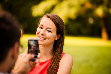 nature photo: Young man taking photo of her girlfriend with mobile phone in nature