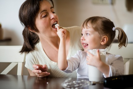 finger licking: Mother and her child licking together home-made whipping cream