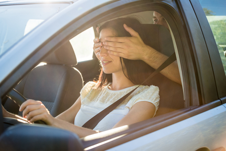 covering: Young couple in car - man covering eyes of his girlfriend