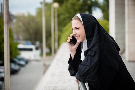 phone calls: Young nun in black dress calls phone - outdoors setting