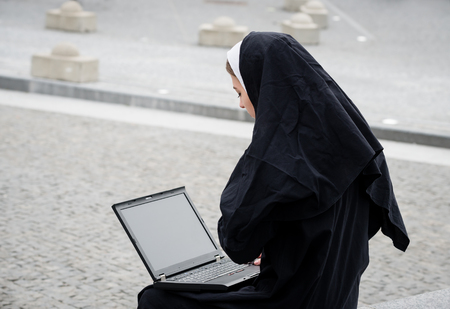 Catholic nun working on computer - outside in street Stock Photo