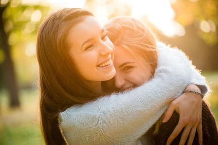 chicas adolescentes: Dos amigos - muchachas adolescentes que se abrazan al aire libre en el otoño al atardecer