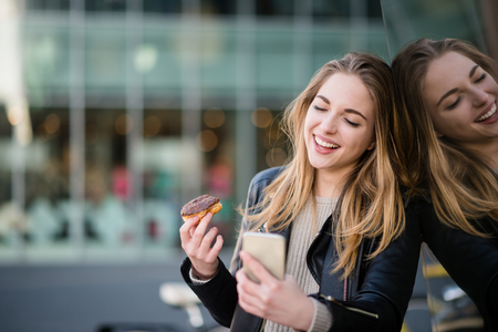 Smiling woman eating donut and messaging with friends on phone in street