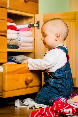 chest of drawers: Baby throws out clothes from wooden furniture at home