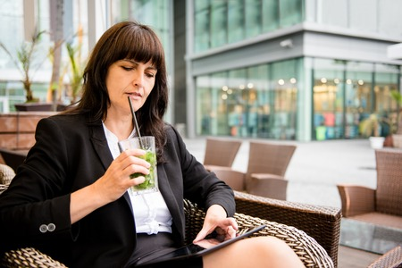 woman bar: Senior business woman drinking mojito outdoor in street bar and working on tablet Stock Photo