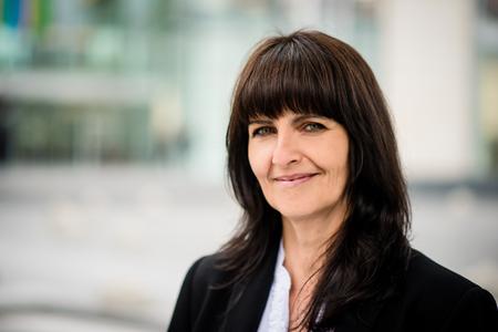 Portret van glimlachende vertrouwen senior business vrouw in een straat