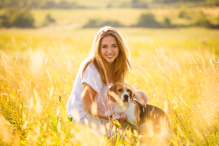 Teen girl having fun with beagle dog outdoor in nature on sunny summer day