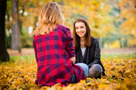 confide: Two friends -  teenage girls talking outdoor in autumn - sitting on ground in leaves