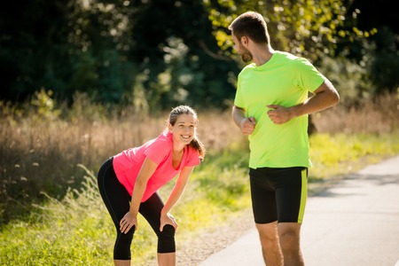 turns: Young woman resting during jogging in park while man running and turns on her Stock Photo
