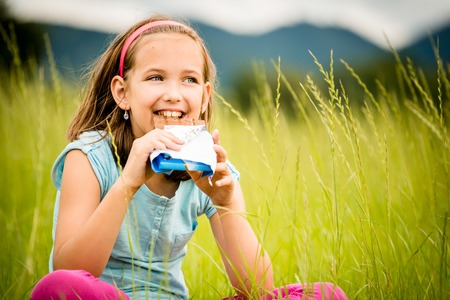relishing: Smiling child eating and relishing chocolate - outdoor in nature