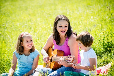 Woman playing guitar to her children in nature on sunny summer day photo