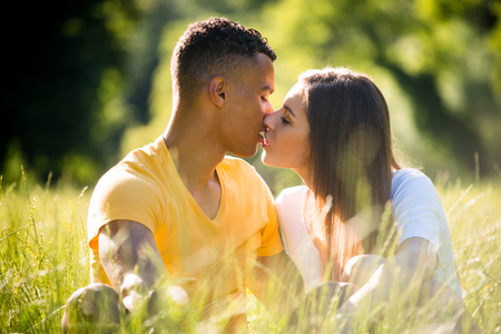 grassfield: Young mixed ethnic couple kissing outdoor on summer day Stock Photo