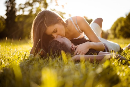 racial: Young multi racial couple kissing in nature on grass - woman lies on man